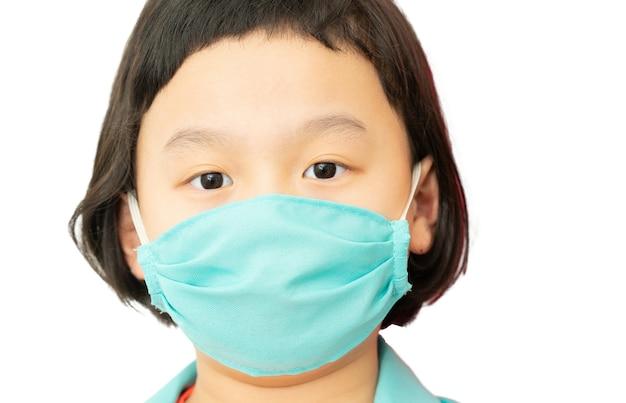 Groene kleur chirurgisch beschermen masker op azië kind dokter jurk gezicht, kijk naar camera, headshot portret, geïsoleerd op wit