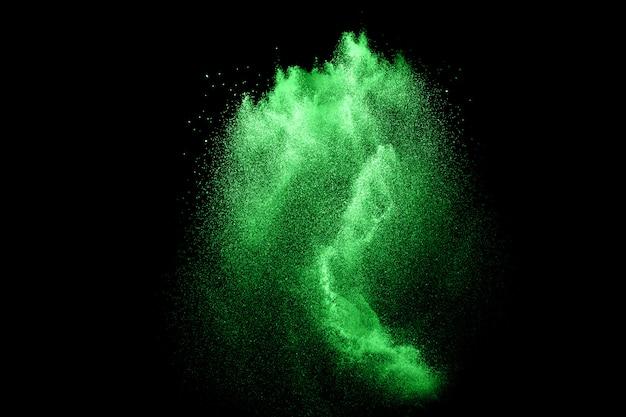 Groene kleur poeder explosie wolk op zwarte achtergrond.