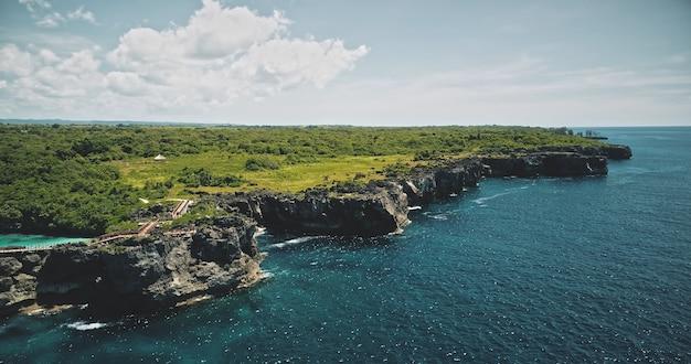 Groene klifkust van overzeese baai met smaragdgroen meer bovenop
