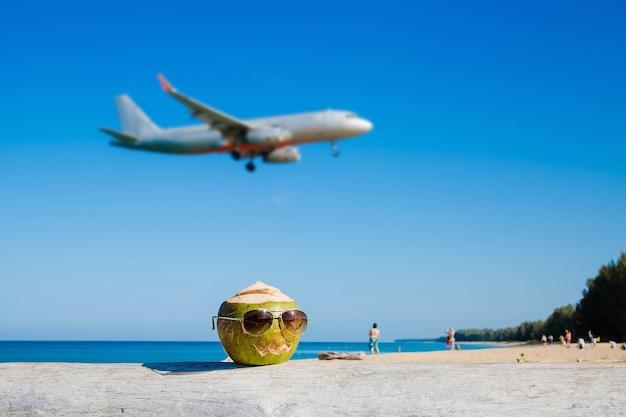 Groene kokosnoot met zonnebril op het strand in pompoenvorm voor halloweenconcept opstijgen vliegtuig