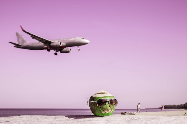 Groene kokosnoot met zonnebril op strand pompoen in de vorm van halloween opstijgen vliegtuig