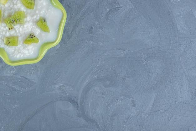 Groene kom gevuld met melkachtige rijst en bedekt met stukjes kiwi op marmeren achtergrond.