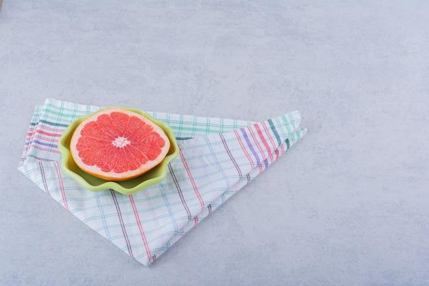 Groene kom verse grapefruitplak op steen.