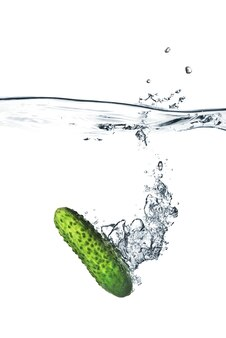 Groene komkommer gedaald in water geïsoleerd op wit