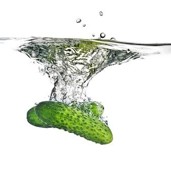 Groene komkommers gedaald in water geïsoleerd op wit