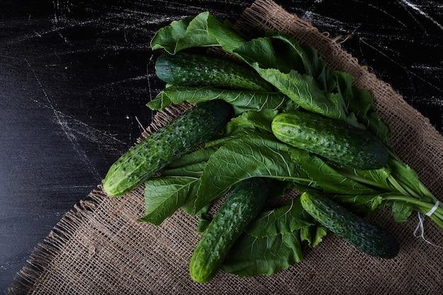 Groene komkommers op plantenbladeren.