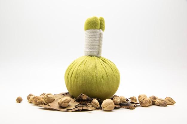 Groene kompresbal met veel kruiden op wit.
