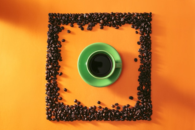 Groene kop koffie in het midden van de koffiebonen van de quare-vorm op oranje achtergrond