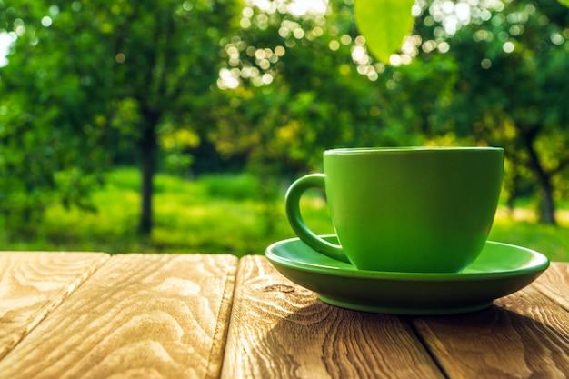 Groene kop warme koffie op een houten tafel in een groene tuin in de ochtend of avond