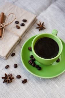 Groene kopje koffie met koffiebonen en anijs ster
