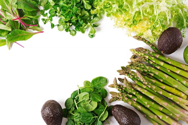 Groene kruiden, asperges en zwarte avocado op een witte achtergrond. bovenaanzicht plat leggen