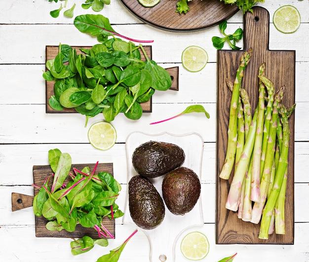Groene kruiden, asperges en zwarte avocado op een witte houten achtergrond. bovenaanzicht plat leggen