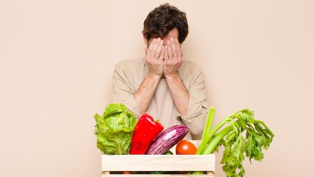 Groene kruidenier man verdrietig, gefrustreerd, nerveus en depressief, gezicht met beide handen, huilen