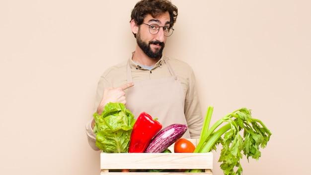 Groene kruideniersmens die gelukkig, trots en verrast kijkt, vrolijk naar zichzelf richtend, zelfverzekerd en verheven voelt