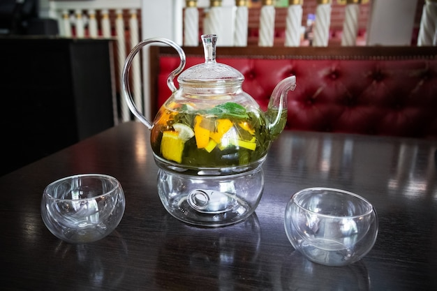 Groene kruidenthee in een transparante glazen theepot en twee glazen kopjes op een houten tafel.