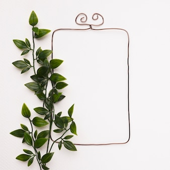 Groene kunstbladeren in de buurt van het rechthoekige frame op witte muur