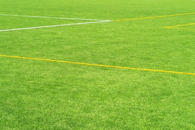 Groene kunstgras gras voetbal voetbalveld achtergrond met witte en gele lijn grens. bovenaanzicht
