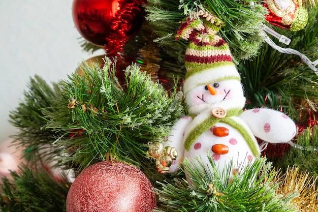 Groene kunstmatige kerstboom versierd met mooie lachende textiel sneeuwpop, rode ballen en ander speelgoed. woondecoratie voor een gezinsvakantie. selectieve focus