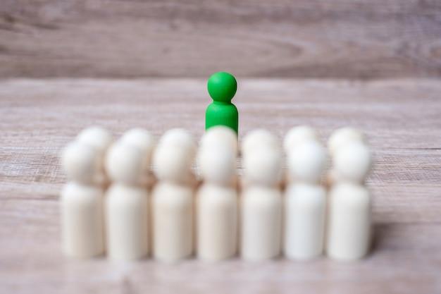 Groene leiderszakenman met menigte van houten mensen. leiderschap, business, team, teamwork en human resource management