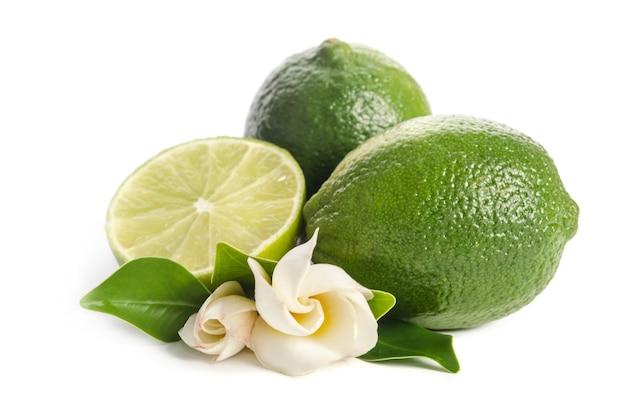 Groene limoenen met de helft van sappige limoen en prachtige bloem geïsoleerd