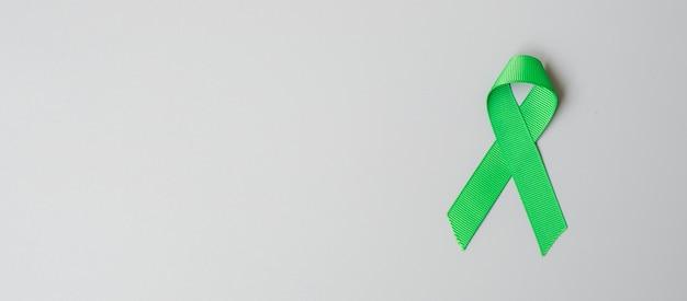 Groene lintkleur op grijze achtergrond voor het ondersteunen van mensen die leven en ziek zijn.