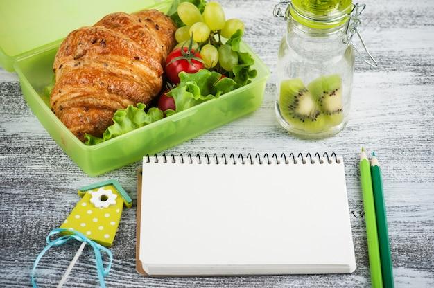 Groene lunchbox met croissant, salade