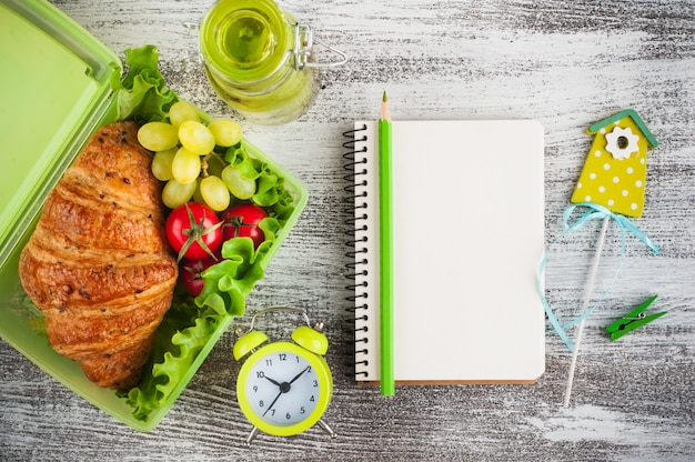 Groene lunchbox met snack en een laptop
