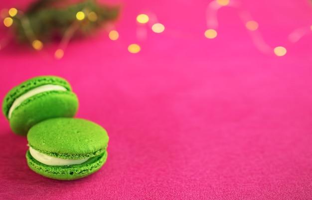 Groene macaron met fondantje op rode papier achtergrond. bij een tak van een kerstboom met een slinger. close-up, copyspace.