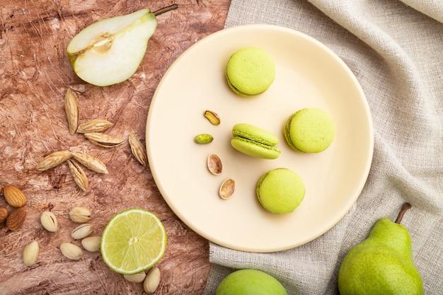 Groene macarons of bitterkoekjes taarten met kopje koffie op een bruine betonnen achtergrond en linnen textiel. bovenaanzicht, platliggend,