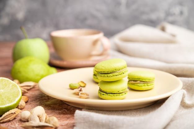 Groene macarons of bitterkoekjes taarten met kopje koffie op een bruine betonnen achtergrond en linnen textiel. zijaanzicht, close-up,