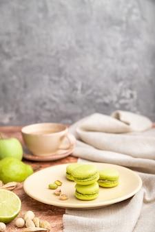 Groene macarons of bitterkoekjes taarten met kopje koffie op een bruine en grijze betonnen achtergrond en linnen textiel. zijaanzicht, kopie ruimte,