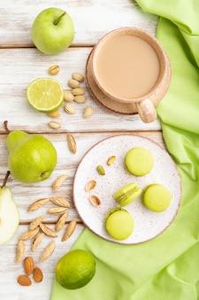 Groene macarons of bitterkoekjes taarten met kopje koffie op een witte houten oppervlak en groen linnen textiel