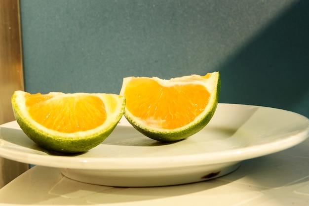 Groene mandarijn in stukjes gesneden liggend op een witte plaat.