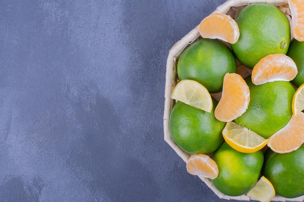 Groene mandarijnen in een bamboemand op blauwe tafel.