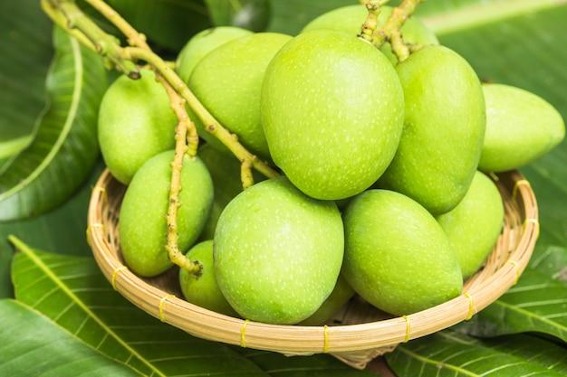 Groene mango's in mand en bladeren op de vrije ruimte van de houten vloer.