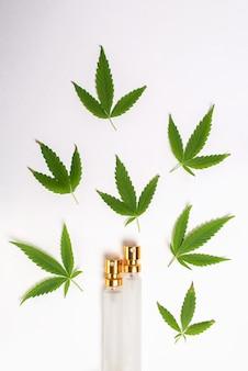 Groene marihuanabladeren en flessen bovenaanzicht op een witte achtergrond