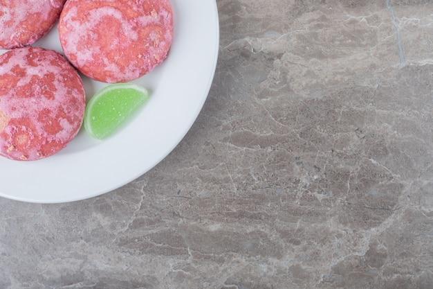 Groene marmelades en roze koekjes op een schaal op marmeren ondergrond