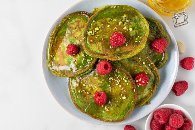 Groene matcha zelfgemaakte pannenkoeken met verse frambozen, pistache en honing op wit