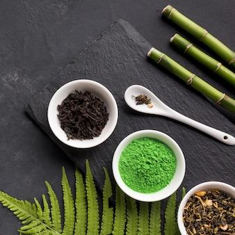 Groene matchathee en droog theekruid met bamboestok over zwarte steenachtergrond