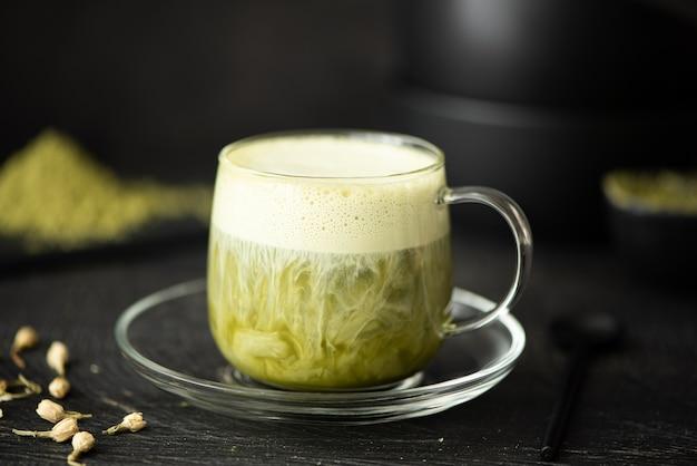 Groene matchathee met melk in een glazen beker