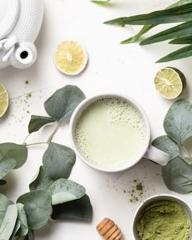 Groene matchatheebladen en kalk op een lijst
