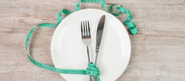 Groene meetlint gewikkeld rond mes en vork met witte keramische schotel op houten tafel achtergrond