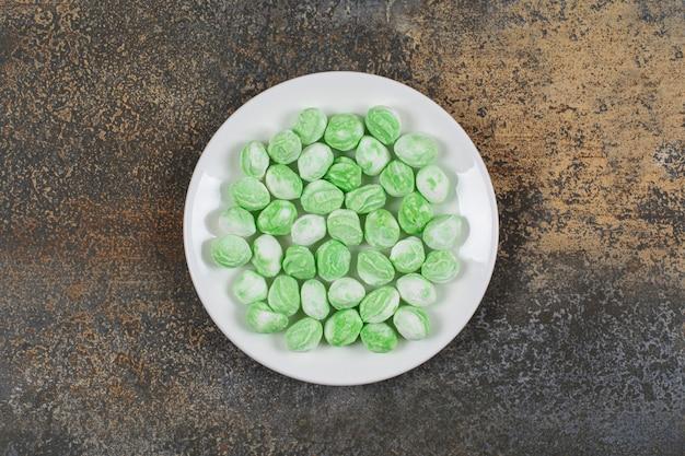 Groene mentholsuikergoed op witte plaat.