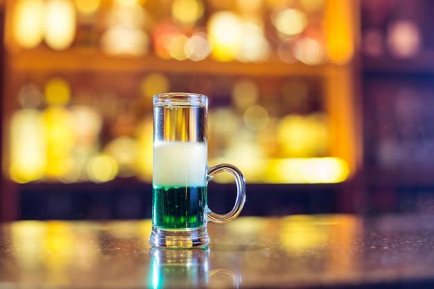 Groene mexicaan aan de bar. meerlaagse brandende alcoholische cocktail. detailopname