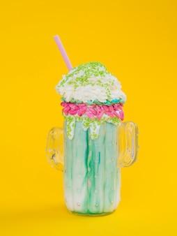 Groene milkshake op gele achtergrond