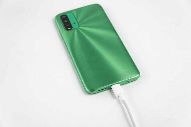 Groene mobiele telefoon aangesloten op usb-kabel type c - opladen