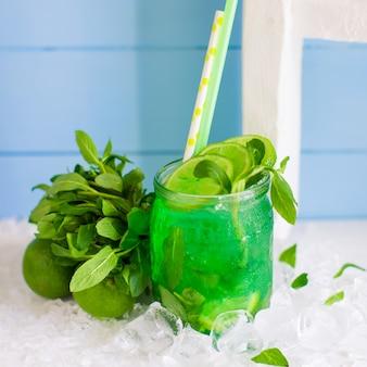 Groene mojito geserveerd in glazen pot gegarneerd met limoen en munt