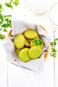 Groene muntkoekjes op een servet in rieten mand, melk in een glas en een kruik op de achtergrond van een licht houten bord van bovenaf