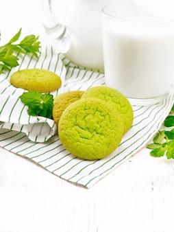 Groene muntkoekjes op een servet met melk in een glas op witte houten raadsachtergrond