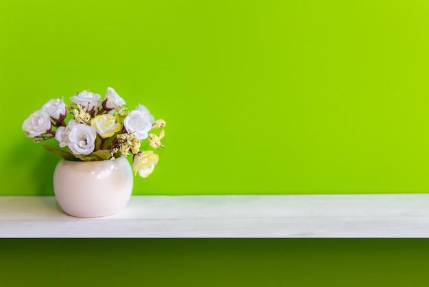 Groene muur met bloemen op planken wit hout, exemplaarruimte voor test. stilleven concept